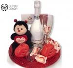 Poklon paket sadrži: JP CHENET ICE EDITION, plišana bubamara koja govori I love you, svećnjak, čašu za šampanjac, raffaello kuglice, čokoladne praline bombonjeru i crvenu veliku tacnu